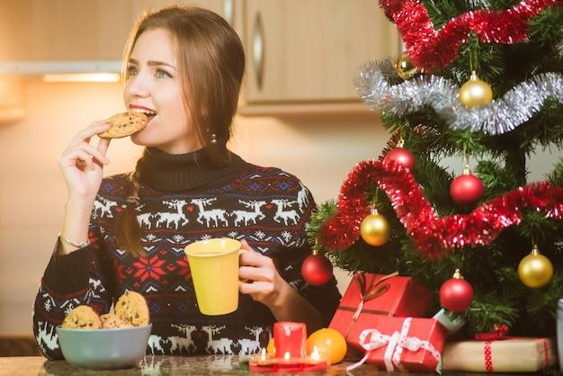 Jovem mulher feliz comendo biscoitos de chocolate perto da árvore de natal