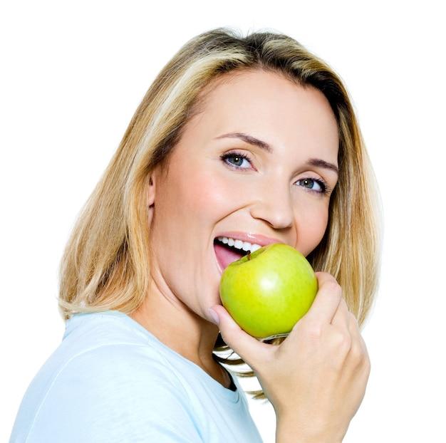 Jovem mulher feliz comendo maçã verde