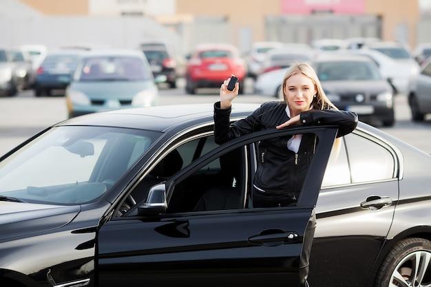 Jovem mulher feliz comprou carro moderno novo.