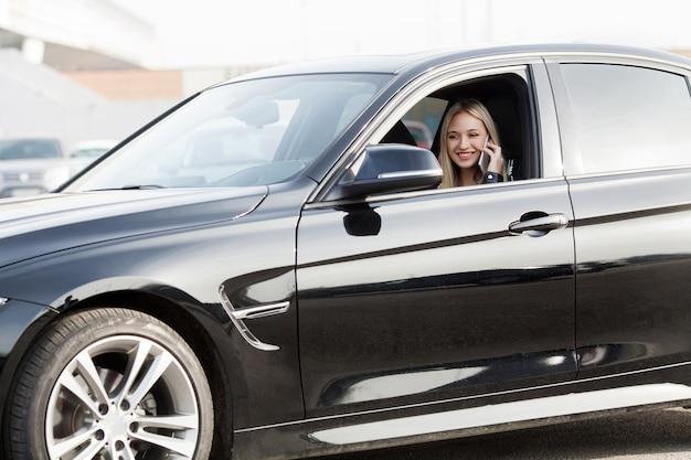 Jovem mulher feliz comprou carro moderno novo