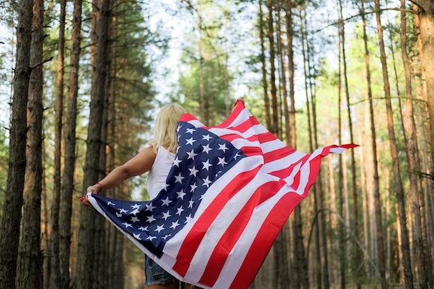 Jovem mulher feliz correndo e pulando despreocupado com os braços abertos sobre o campo de trigo. segurando a bandeira dos eua. imagem enfraquecida.