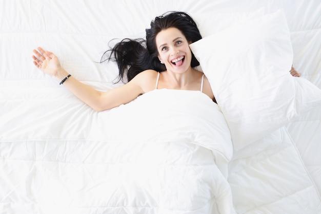 Jovem mulher feliz deitada na cama e mostrando a língua de cima