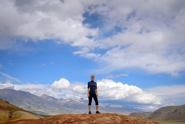 Jovem mulher feliz do atlético construir em roupas apertadas fica no topo da montanha contra o céu azul em dia ensolarado.