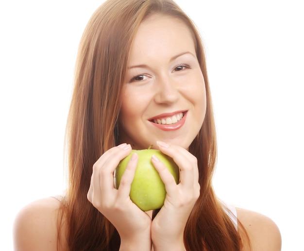Jovem mulher feliz e sorridente com maçã, isolada no branco
