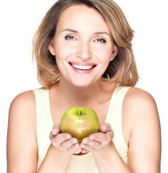 Jovem mulher feliz e sorridente com maçã verde isolada no branco.