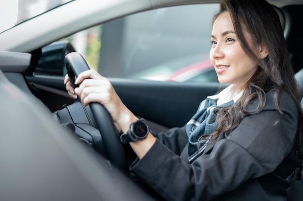 Jovem mulher feliz e sorridente dirigindo um carro novo