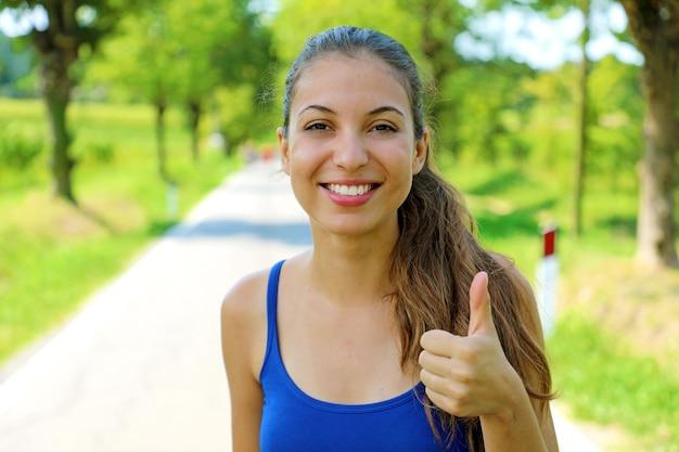 Jovem mulher feliz em boa forma mostrando o polegar ao ar livre