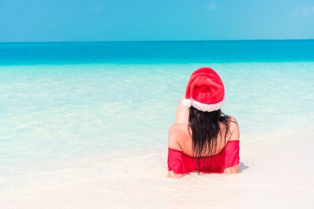 Jovem, mulher feliz, em, chapéu santa, em, swimsuit, branco, praia, ligado, xmas, feriados