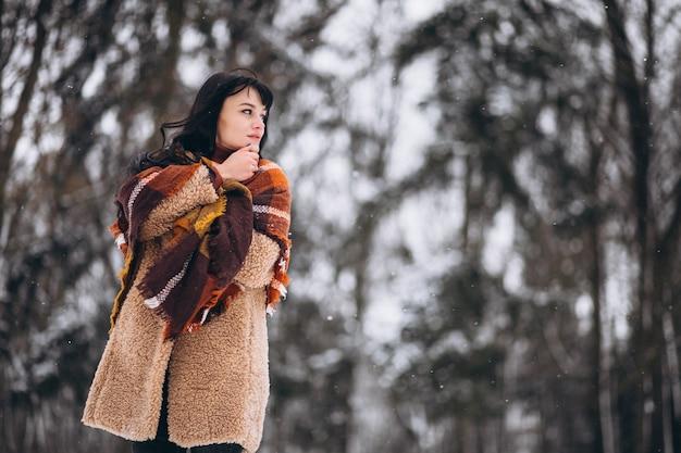 Jovem mulher feliz em panos quentes em um parque de inverno