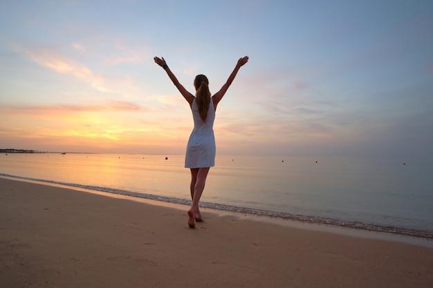 Jovem mulher feliz em pé na praia à beira-mar, desfrutando de uma noite tropical quente.