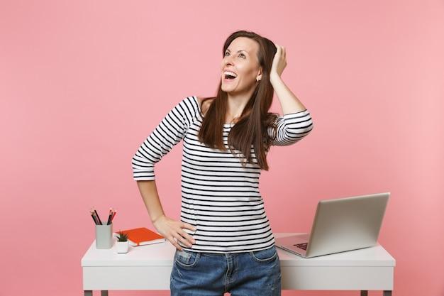 Jovem mulher feliz em roupas casuais, sonhando procurando trabalho em pé perto da mesa branca com laptop isolado em fundo rosa pastel. conceito de carreira empresarial de realização. copie o espaço para anúncio.