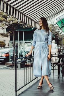 Jovem mulher feliz em um café de rua sorrindo risos bebendo café em um terraço