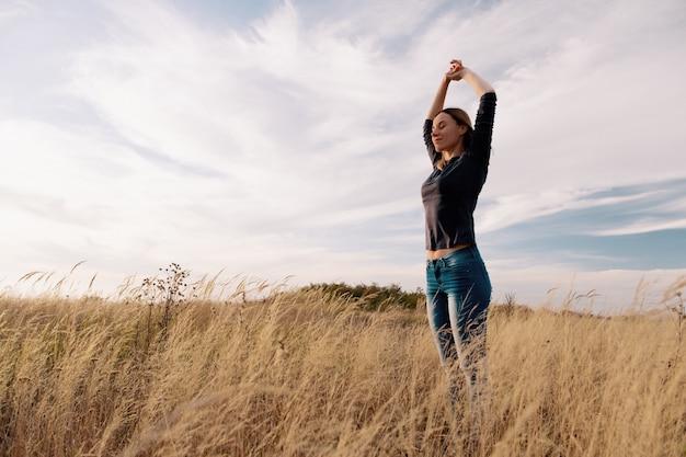 Jovem mulher feliz em um campo dourado na sunset.