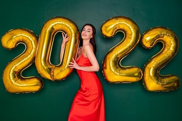 Jovem mulher feliz em um vestido vermelho segurando balões dourados com o conceito de ano novo de fundo verde