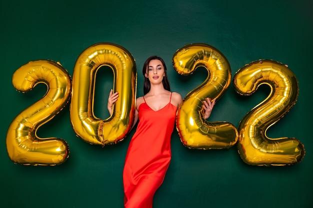 Jovem mulher feliz em um vestido vermelho segurando balões dourados sobre fundo verde conceito de ano novo