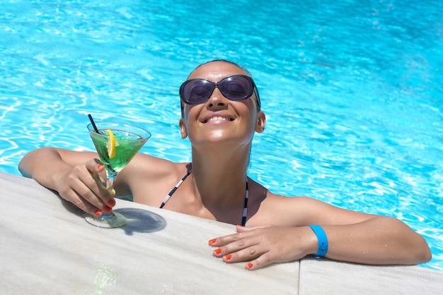 Jovem mulher feliz em uma piscina com um copo de coquetel verde delicioso sob a luz do sol