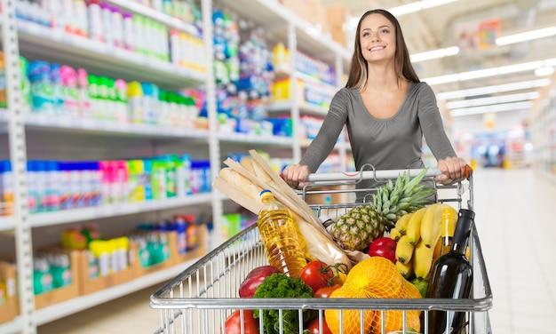 Jovem mulher feliz empurrando carrinho de compras