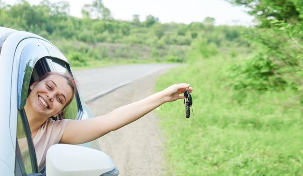 Jovem mulher feliz está sentada no carro, segurando as chaves na mão. a menina fica feliz com a compra, obtendo a carteira de habilitação.