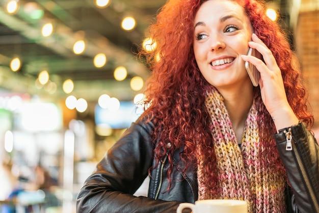 Jovem mulher feliz falando ao telefone na cafeteria.