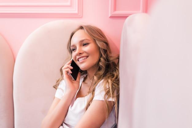 Jovem mulher feliz falando no celular com um amigo enquanto está sentada sozinha no interior de uma cafeteria moderna