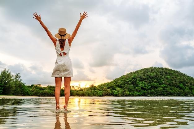 Jovem mulher feliz levantando as mãos apreciando o lindo pôr do sol