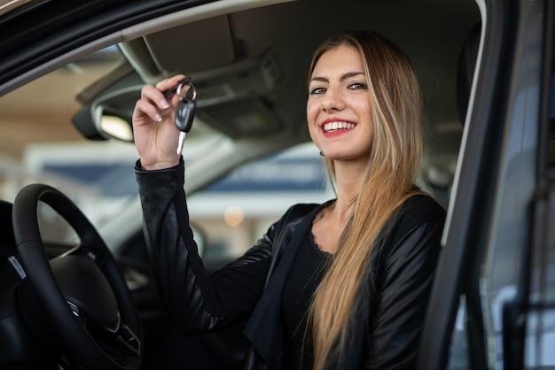 Jovem mulher feliz mostrando a chave de seu carro novo em um salão de uma concessionária