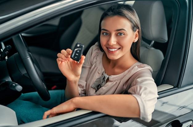 Jovem mulher feliz mostrando a chave do carro novo. mulher comprando o carro.