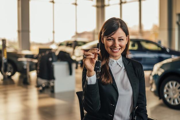 Jovem mulher feliz mostrando a chave do carro novo.