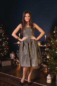 Jovem mulher feliz na acolhedora sala com decorações de natal