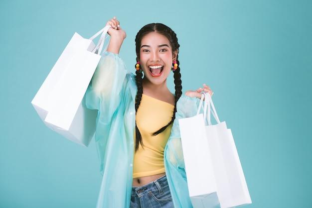 Jovem mulher feliz na capa de chuva com os sacos de compras, comprando no conceito da venda do dia chuvoso.