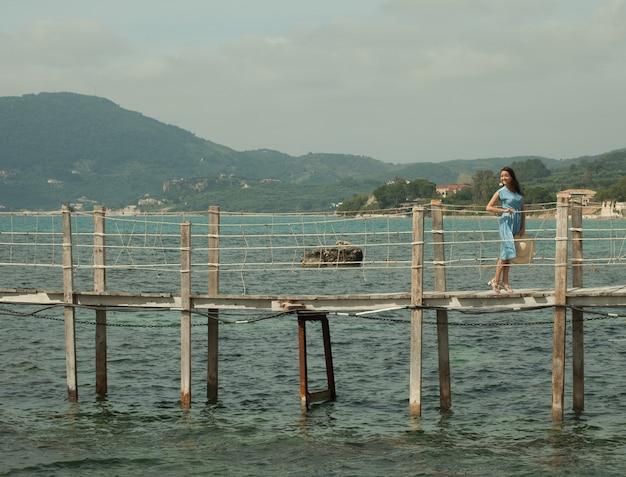 Jovem mulher feliz na ponte perto do mar