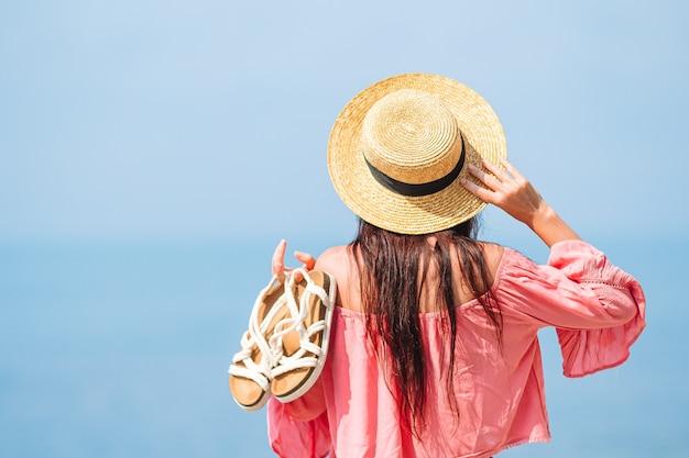 Jovem mulher feliz na praia com vista para a montanha