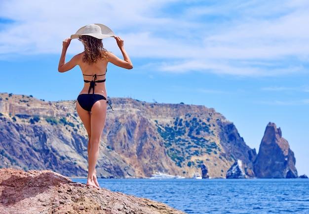 Jovem mulher feliz no beira-mar que aprecia férias.
