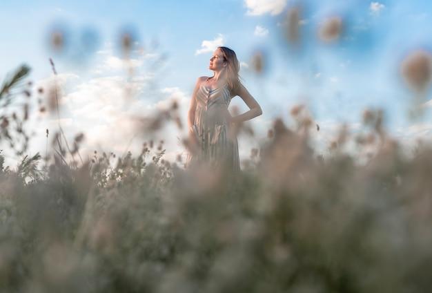 Jovem mulher feliz no campo de verão, aproveitando a liberdade e as férias de verão