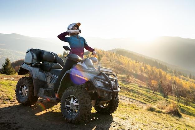 Jovem mulher feliz no capacete protetor, desfrutando de passeio extremo na moto atv quad nas montanhas de outono ao pôr do sol.