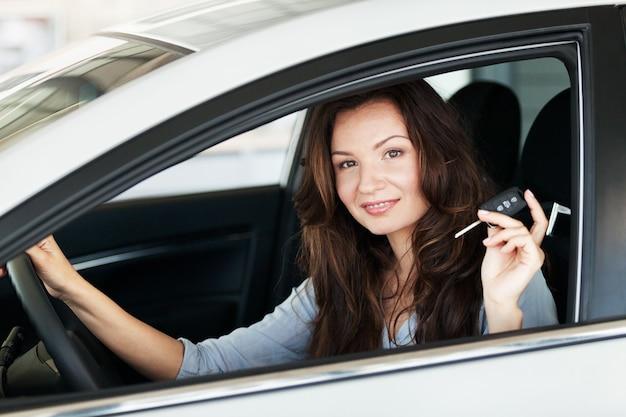 Jovem mulher feliz no carro com as chaves sorrindo - conceito de comprar carro