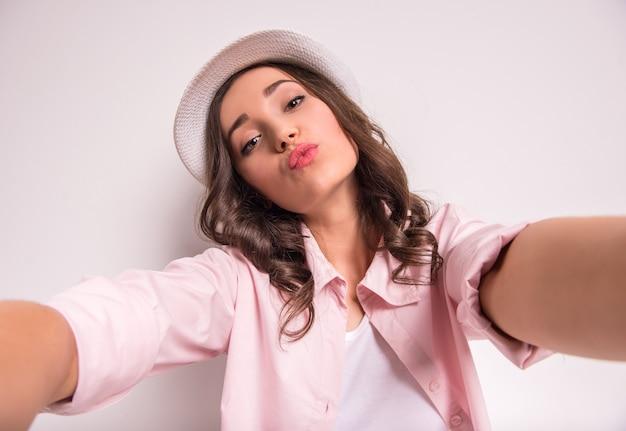 Jovem mulher feliz no chapéu está fazendo foto de selfie.