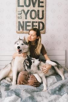 Jovem mulher feliz no vestido marrom, sentado na cama e abraçando adoráveis cachorros husky.