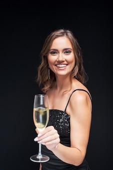 Jovem mulher feliz num vestido elegante com taça de champanhe na festa.