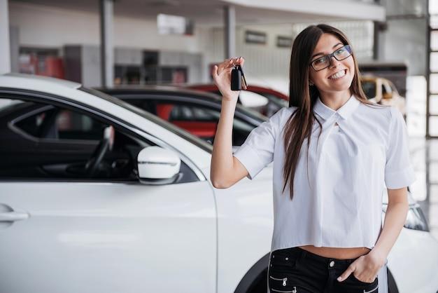 Jovem mulher feliz perto do carro com as chaves na mão