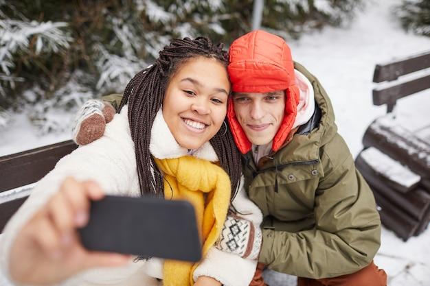 Jovem mulher feliz posando para a câmera de seu telefone celular junto com um homem enquanto eles estão sentados no banco no inverno