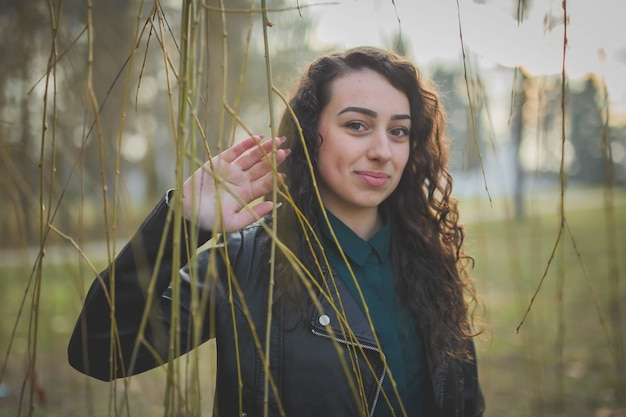 Jovem mulher feliz posando perto de juncos em um parque