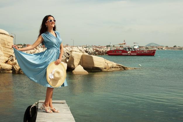 Jovem mulher feliz posando perto do mar