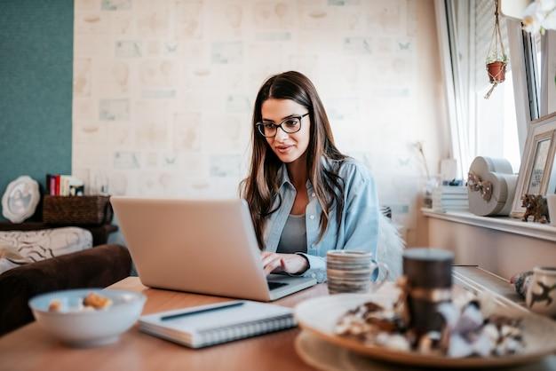Jovem mulher feliz que estuda no portátil em seu apartamento.