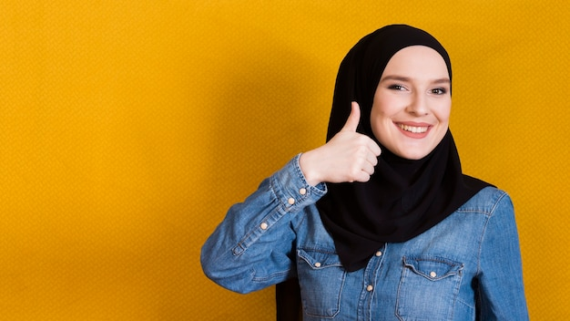 Jovem mulher feliz que gesticula o thumbup contra a superfície amarela brilhante