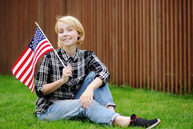 Jovem mulher feliz que guarda a bandeira americana. conceito do dia da independência.