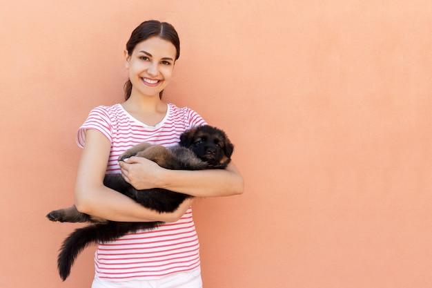 Jovem mulher feliz que guarda seu cachorrinho de estimação no fundo alaranjado