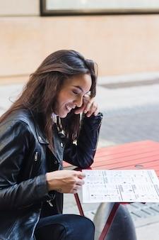 Jovem mulher feliz que lê o cartão do menu ao sentar-se no café exterior
