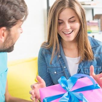 Jovem mulher feliz que recebe o presente de seu marido