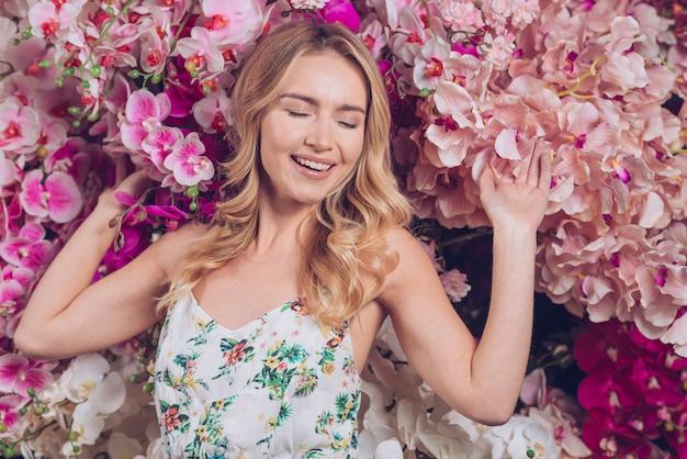Jovem mulher feliz que sente relaxado com ramos de flores de uma orquídea
